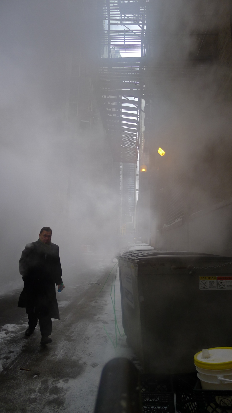 man walking through alley and smoke